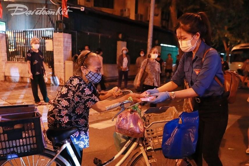 Điểm đến tiếp theo của đoàn dừng tại phố Trần Bình Trọng. Từng cụ già, bà bầu hay những người có hoàn cảnh khó khăn xếp hàng nhận từng suất ăn. Ảnh: Quang Vinh.