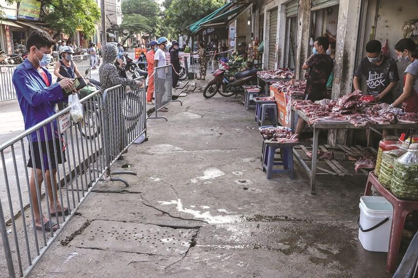 Người dân mua hàng ở phía ngoài cổng chợ phải xếp hàng và giữ khoảng cách tại các kiốt.